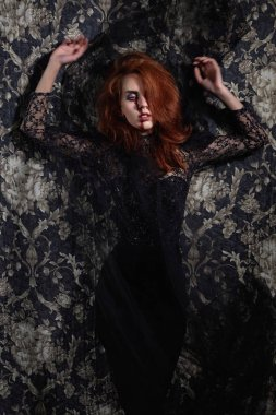 woman with a bloody face make-up over flower background.halloween black widow.red hair girl in black dress