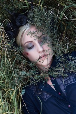 dead woman in grass.halloween idea. zombie girl with black flowers on her head