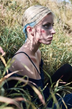 beaten girl.bloody halloween make-up.sad woman with blood on her face