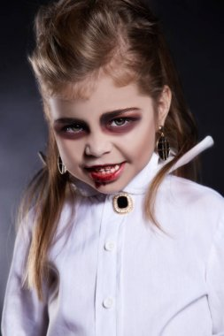 little vimpire child.little angry girl with halloween make-up.dracula kid with blood on her face.halloween holiday children