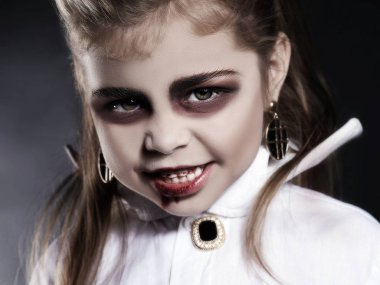 little vimpire child. little angry girl with halloween make-up. dracula kid with blood on her face. halloween holiday children