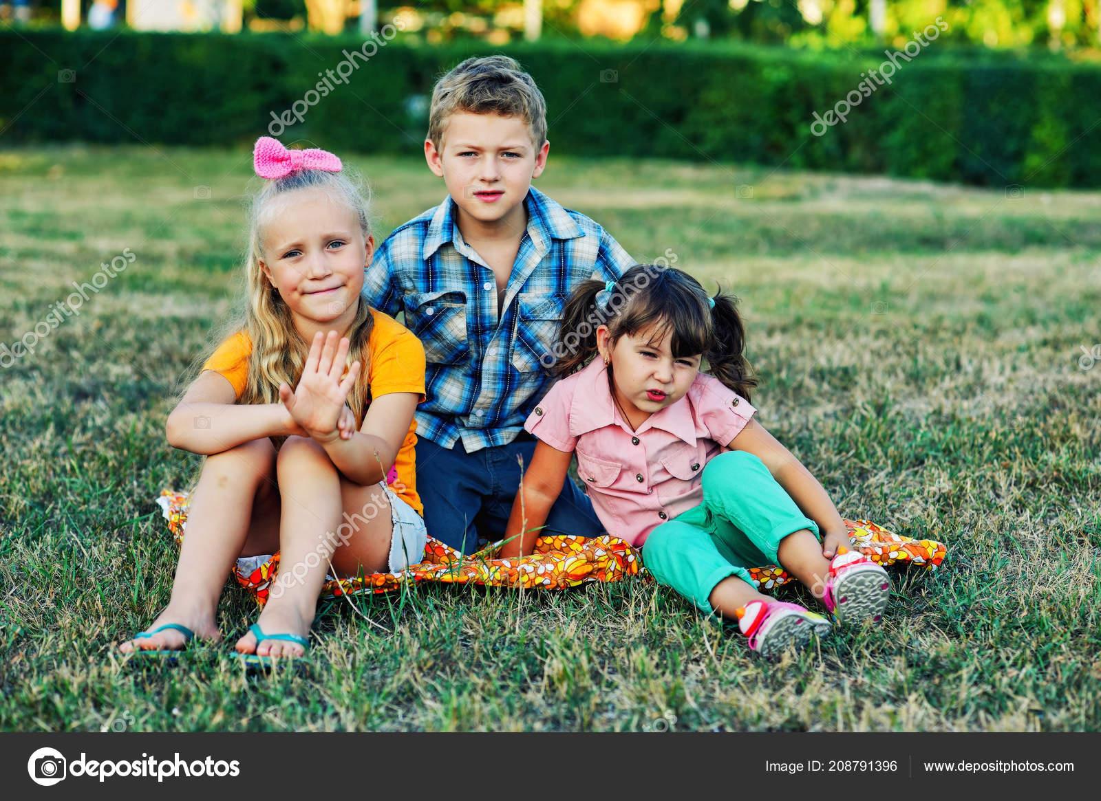 0dfff9ffb73 Αστεία χαριτωμένα παιδιά να παίζουν στο γρασίδι. Φίλοι τα παιδιά να  διασκεδάσουν με τα πόδια — Εικόνα από ...