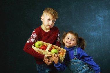 Brother and sister holding a basket of apples on a dark background