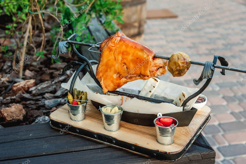 pigs with an apple on a sword; ready shank in the open air; a few leuces lie around the meat; cooked meats