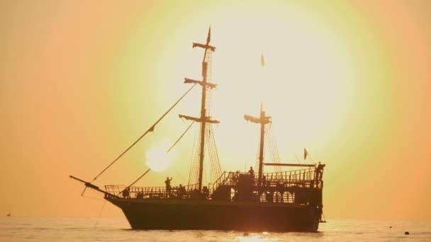 Krásný západ slunce. Loď pluje na vlnách při západu slunce. Moře chodit na moře loď. Silueta lodi při západu slunce