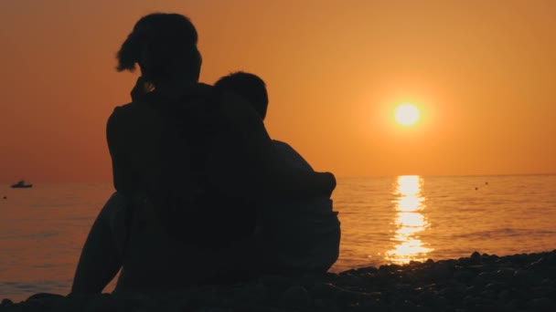 Back view of mom and son, silhouette, sitting hugging. Travel and enjoy the rays of the setting sun. Amazing sunset on the beach in summer. Happy family. Family value. Love and support of parents