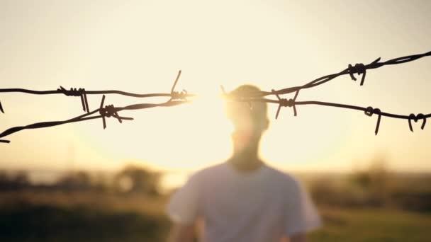 Der Junge steht bei Sonnenuntergang hinter Stacheldraht. Hände, die den Draht halten. Einwanderungskonzept. Silhouette eines Kindes hinter einem Zaun