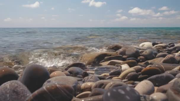 Velké oblázkové kameny u moře. Mořské vlny pomalý pohyb na oblázkové kameny
