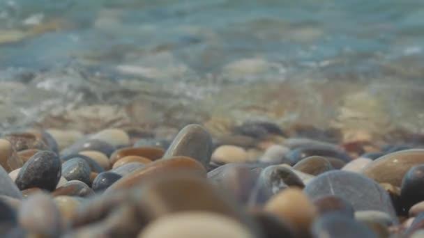 Oblázková pláž moře. jsou pomalé vlny na pobřeží. Detailní záběr.