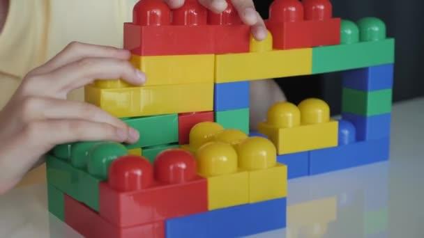 Detail ruky chlapci sbírání rozvíjející návrháře lego u bílého stolu. Koncept šťastné dětství