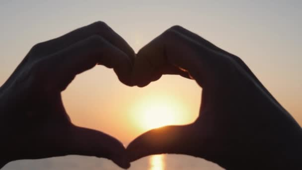 Female hands close-up in the shape of a heart in the sky pass the rays of the sun. Hands in the shape of a love heart at sea