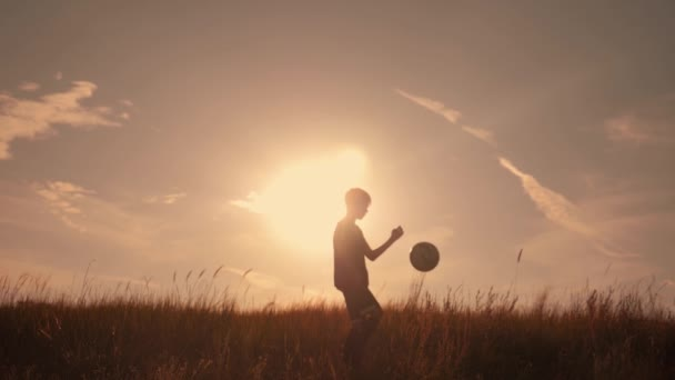 Silhouette of a boy playing football at sunset. A boy juggles a ball in the field at sunset