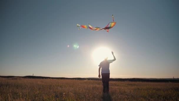 Egy fiú a mezőn fut a naplemente a sárkányeregetés a feje fölött. Chidhood álom. Gyerekek játékkal