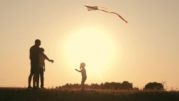 Šťastná rodina. Rodina v létě při západu slunce zahájit draka do nebe.