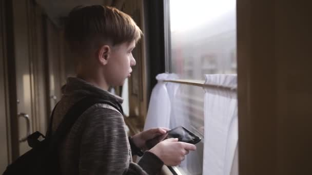 The boy stands at the train window with a tablet in his hands. Travel by train. Vacation tourism, traveling the world