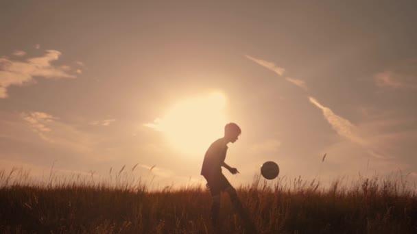 Sziluettjét egy fiú focizni a naplemente. Egy fiú juggles a labdát, a mező a naplemente