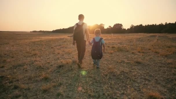 Two travelers boy. Two boys are walking along the field at sunset with rucksacks. The concept of family and travel