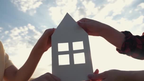 Nahaufnahme von Händen, die ein Papiermodell zu Hause auf einem Feld bei Sonnenuntergang halten. Silhouette eines Papierhauses in den Strahlen der untergehenden Sonne. Traum vom eigenen Haus