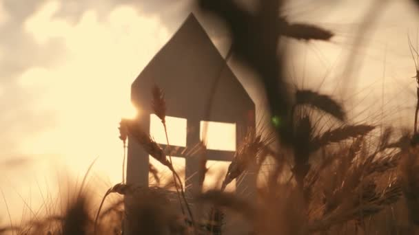 Close-up of hands holding a paper model at home in a field at sunset. Silhouette of a paper house in the rays of the setting sun. Dream of own house
