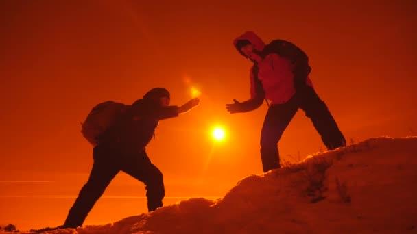 Der Mann mit dem Rucksack reichte seinem Freund beim Klettern eine helfende Hand. Teamwork. Teamwork, Hilfe in schwierigen Situationen