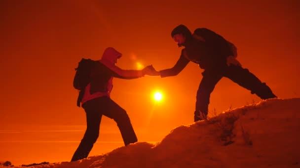 Turistická pomoc kolega stoupání, muž s batohem natáhl pomocnou ruku svého přítele. Koncepce týmové práce. Týmová práce, pomoc v obtížných situacích