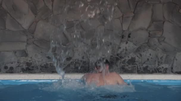 Man doing a back massage. Hydrotherapeutic procedure. Healthy back. Concept: Spa treatments, body massage, swimming pool. Clean, blue water in the pool. Slow motion video.