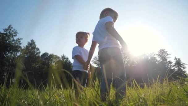 Šťastné děti držící se za ruce jsou na zelené trávě. Užijte si čerstvý vzduch na venkově. Krásná záře slunce.Letní výlet pro děti. Zdravý životní styl.