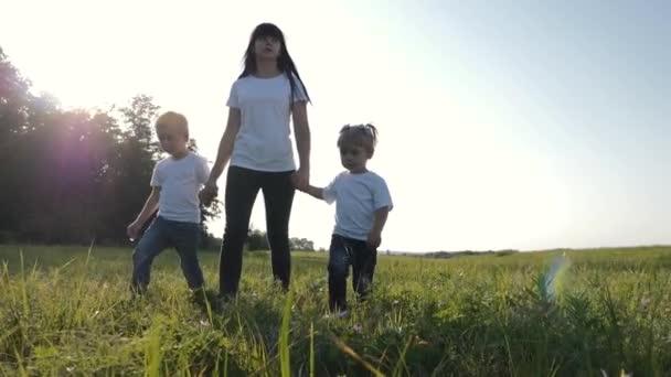 Mladá matka chodí se svými dětmi po zelené trávě. Šťastná rodina se baví trávit svůj den na čerstvém vzduchu.