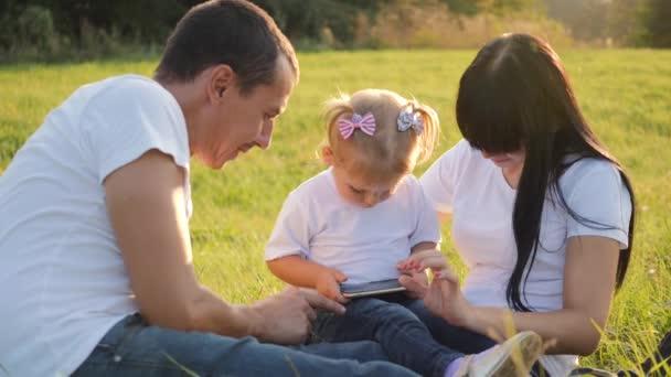 Šťastná rodina tráví čas venku, máma s tátou sedí na trávě se svou malou blonďatou dcerou. Šťastné dítě se podívá na obrazovku chytrého telefonu