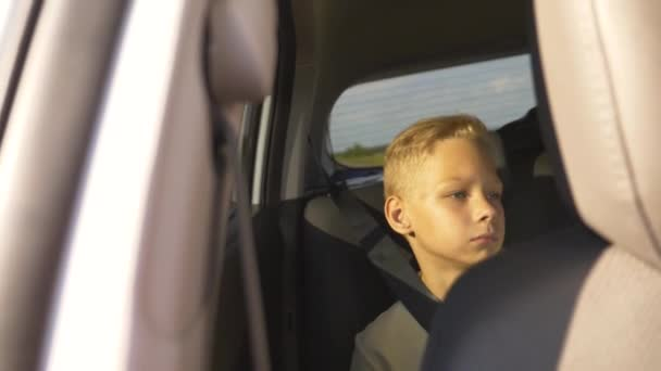 The concept of a family holiday. A school child sits in the back seat of a car and looks out the window enjoying the scenery of the trip. Pensive, dreaming child, sad at the window.