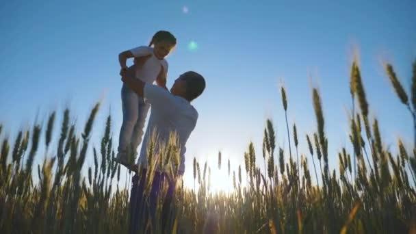 Šťastný otec vyhodí do vzduchu roztomilou holčičku. Táta a dcera si hrají v parku na procházku. Šťastná rodina. Rodina na pšeničném poli při západu slunce.