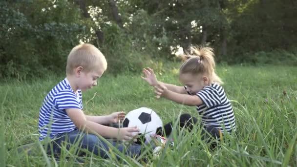Boldog család a parkban a füvön. A gyerekek egy labdával játszanak a parkban.A gyerek megtanulja, hogyan játsszon egy csapatban. Boldog, édes család álmodik. Álomkoncepció. Egy csapat kölyök a parkban. A gyerekek álmodnak.