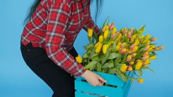 Young female florist with yellow tulips