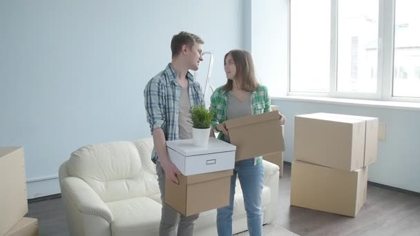 Happy young couple with cardboard boxes moves to new apartment