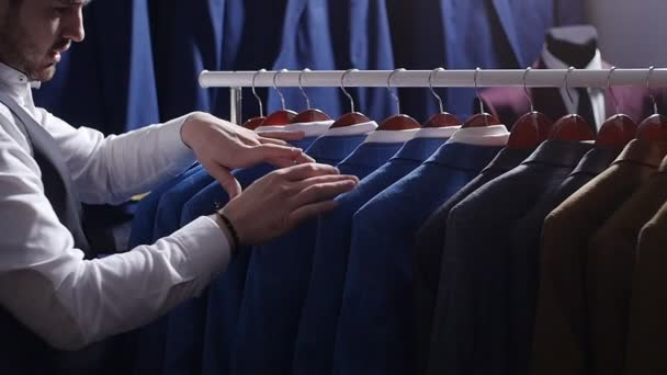 Man choosing business suit at men clothing store