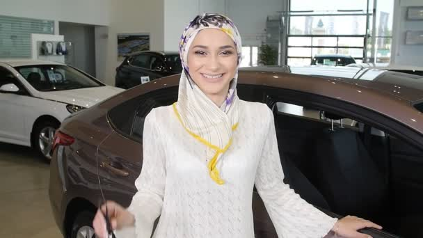 Happy Muslim woman with car key over car show background
