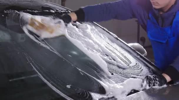 Muž pracovník mytí auta s houbou na mytí aut stanice