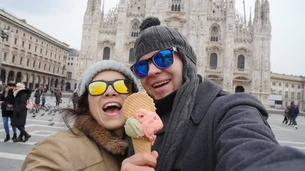 Happy Couple in Milan eating Ice cream taking selfie self-portrait photo on vacation travel in Italy. Winter vacation concept