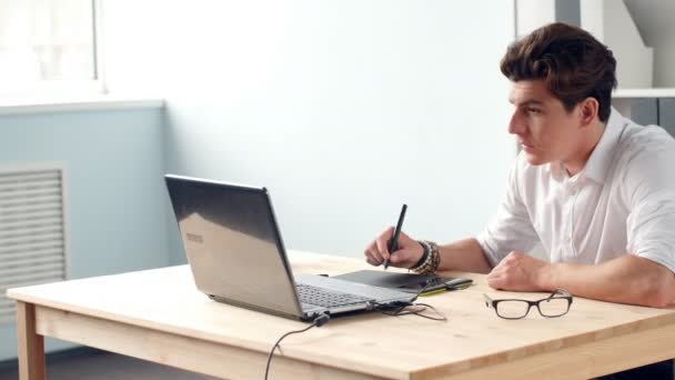 Casual male designer using graphics tablet in a bright office