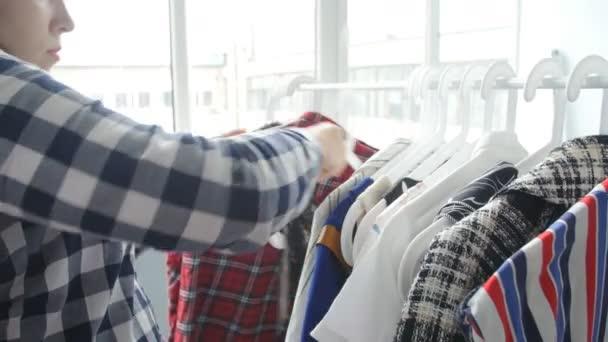 eine junge Frau wählt Kleidung in einem Geschäft