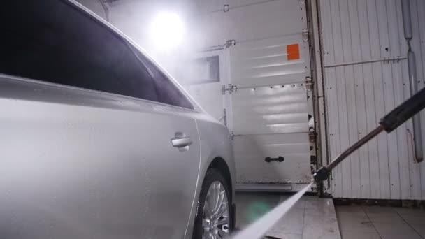 Man washing car under high pressure water indoors