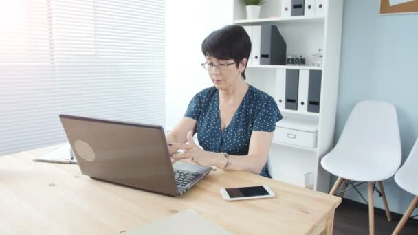 An attractive middle aged businesswoman with a laptop in the office