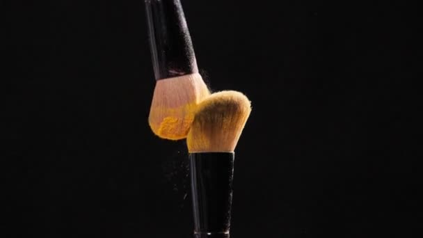 Two Cosmetic brushes with golden cosmetic powder on black background