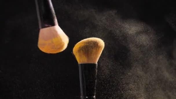 Dvě kosmetické kartáče s golden Kosmetický pudr na černém pozadí