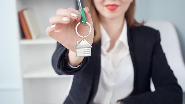 Realitní kanceláře žena dává klíče k bytu pro klienty