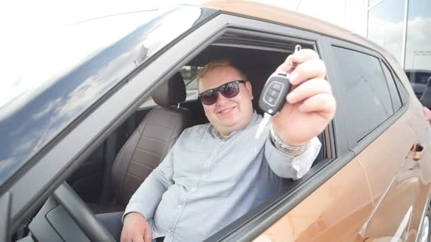 Happy man with keys from new car