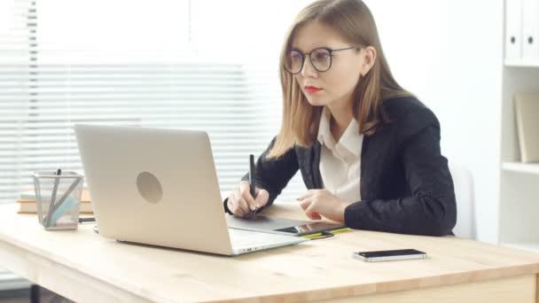 Mladá žena grafický designér pracuje na notebooku pomocí tabletu v moderní kanceláři