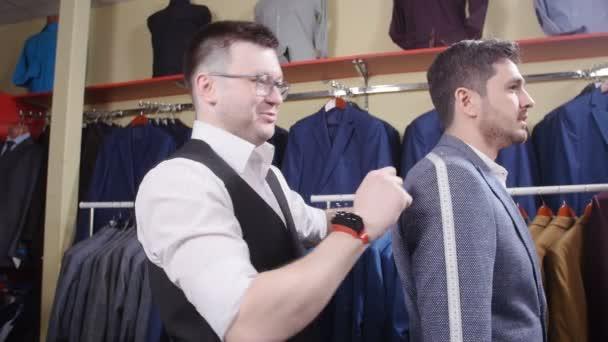 Muž oblek koncept. Prodávající pomáhá kupující zvolit barvu v obchodě s oděvy