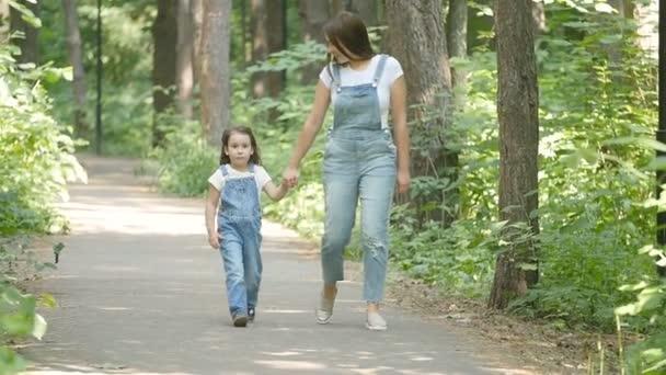 Járműcsalád-koncepció. Fiatal anya és a gyermek lánya kezét, és séta