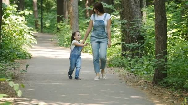 Family concept. Young mother and child daughter holding hands and walk